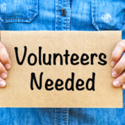 Person holding a sign reading volunteers needed